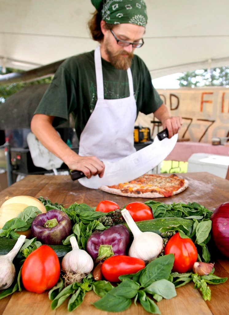 Jeff Knox of Harvest Moon Pizza cuts a pie just baked in the outfit's mobile wood-fired oven.