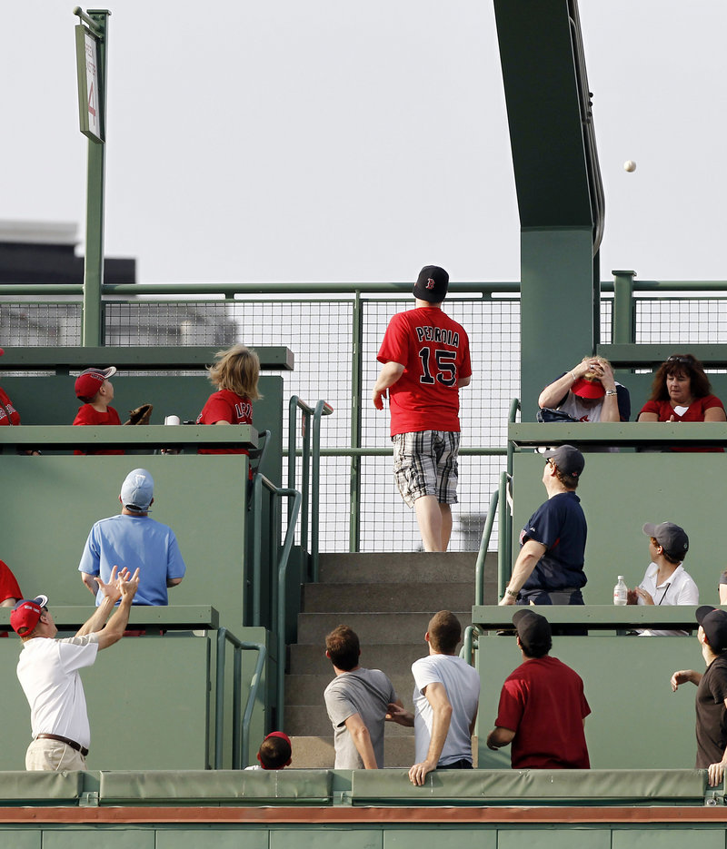Fans atop the Green Monster section of Fenway Park follow the path of Ranger Ian Kinsler's homer as it leaves the park Sunday afternoon.