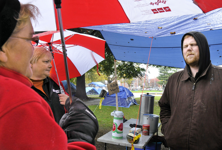 Jason Cook, right, a member of the group Occupy Maine, speaks with nurses Cokie Giles and Cathy Jo Herlihy today about life in the Occupy Maine encampment. Giles and Herlihy were part of a group of nurses, some from the Maine Nurses Association, who donated hats, blankets and medical supplies to the protesters..