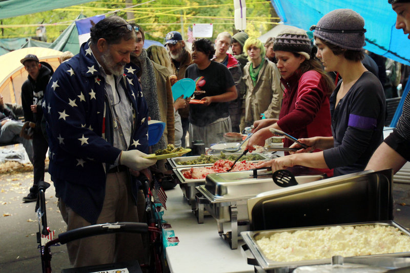 People line up for free lunch at Oregon's Occupy Portland camp last week. Occupy camps nationwide are providing food and shelter to people who were already living outdoors.