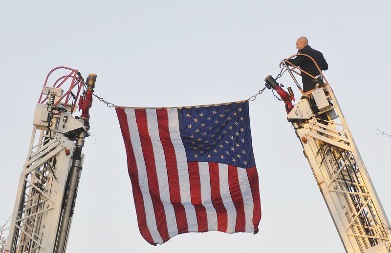 James Westburg of the Portland Fire Department hangs a flag across Ocean Avenue in preparation for the 10 truckfuls of wreaths and the groups accompanying them.
