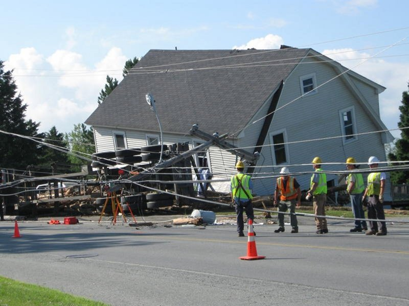 Officials survey the scene of a logging truck accident in July. The truck crashed near a Jackman home, sending logs rolling into the house and killing a 5-year-old boy. The truck driver, Christian Cloutier, will not be prosecuted, the Somerset County District Attorney's Office has decided.