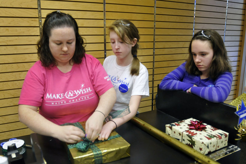 Sabrina Craig of Auburn wraps a gift at the Maine Mall on Sunday to raise funds for Make-A-Wish with her niece Mariah St. Pierre, 14, of Fayette and daughter Hailey Sontag, 11.