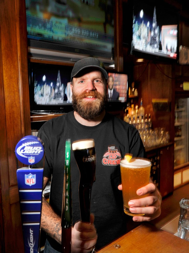 Bartender Marcus Payne serves a draft beer at Binga's Stadium Smokehouse & Sports Bar in Portland, which offers plenty of cocktails and has 28 beers on tap.