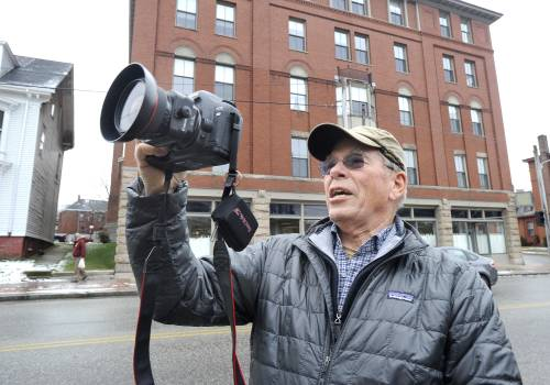Ted Oldham, a volunteer with the Maine Historical Society, takes a photo in Portland Friday.