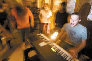 ERIC STEVENSON of Pocket Vinyl sings and plays at the keyboard while listeners groove at the Bombshelter on Saturday night in Brunswick. The informal venue is booked and operated by resident Nick Dentico.