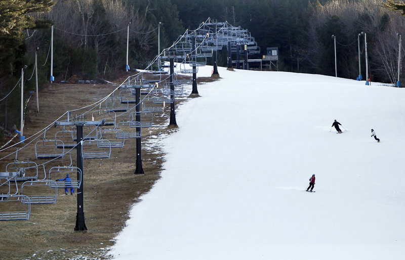 At Shawnee Peak ski area in Bridgton, man-made snow coats a ski run, but barren ground remains under the chairlift Thursday.