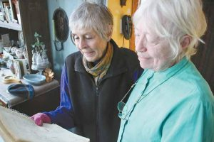 """ELISABETH KING, left, and Maria Holt review old handwritten records of radiation-monitoring """"black boxes"""" at Holt's home in Bath on Friday. The pair are collaborating on a book tentatively titled """"The Death of Maine Yankee: Shutting Down a Nuke."""" Individually and in tandem, the women have worked for decades to educate the public about the hazards of exposure to radiation."""
