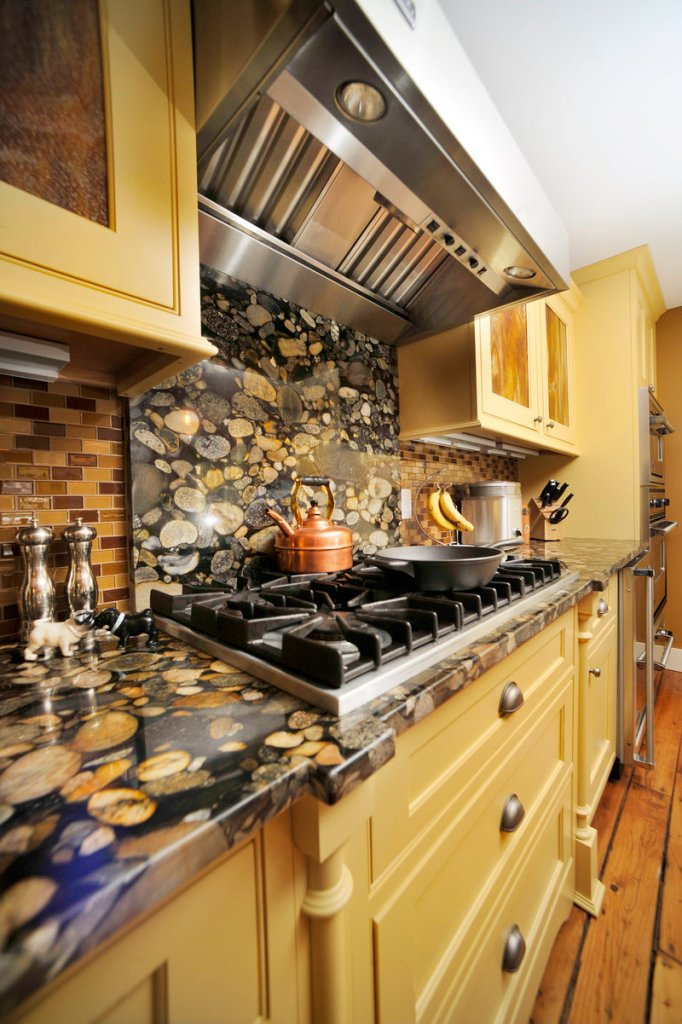 Colors in the countertops and backsplash coordinate with the buttercream-yellow cabinetry.