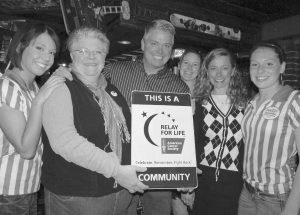 IRENE DUBREUIL, chairwoman of the Relay For Life of Brunswick event committee, second from left, presents a special sign to Troy Kavanaugh — who owns Pedro O'Hara's with wife Shelby Kavanaugh, second from right — designating the restaurant as a Relay For Life community. They are joined by staff members Danielle Kavanaugh, far left, Stacey Curit, fourth from left, and Haley Michaud, far right.
