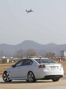 A U.S. AIR FORCE U-2 SPY PLANE approaches to land as a chase car stands by during a training flight in February at the U.S. air base in Osan, South Korea. U-2 pilots in chase cars — at Osan they are white Pontiac G8s — race down the runway at speeds of more than 120 miles per hour to meet each landing. They guide the pilot down, radioing in the plane's altitude as it comes to a full stall with about two feet to go and essentially drops down to the ground.