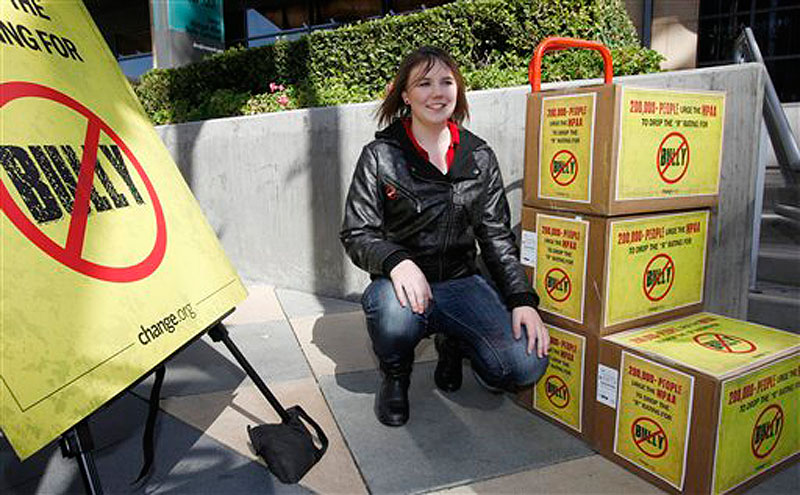 """Katy Butler, 17, a high school student, from Ann Arbor, Mich., poses by the petitions she delivered to the Motion Picture Association of America on Wednesday March 7, 2012, in Los Angeles. Butler is urging the MPAA to change the """"R"""" rating to a """"PG"""" for the """"Bully"""" film. With her petition, Butler said that she was speaking out for all students who suffer every day from bullying. (AP Photo/Damian Dovarganes)"""