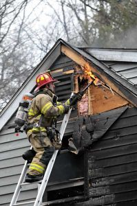 Lisbon Falls Fire Captain William Wallace Jr. opens up a wall to extinguish an area where the fire had spread. (Photo courtesy of Michael Brillant)