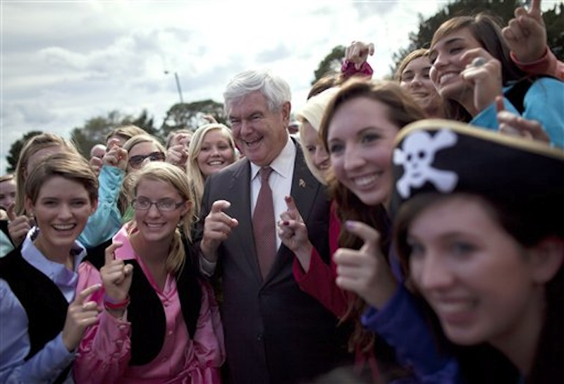 """Republican presidential candidate Newt Gingrich poses for photos with the """"Pirates of the Spanish Maine"""" high school sorority before a rally, Friday, March 2, 2012, in Brunswick, Ga. (AP Photo/Evan Vucci)"""
