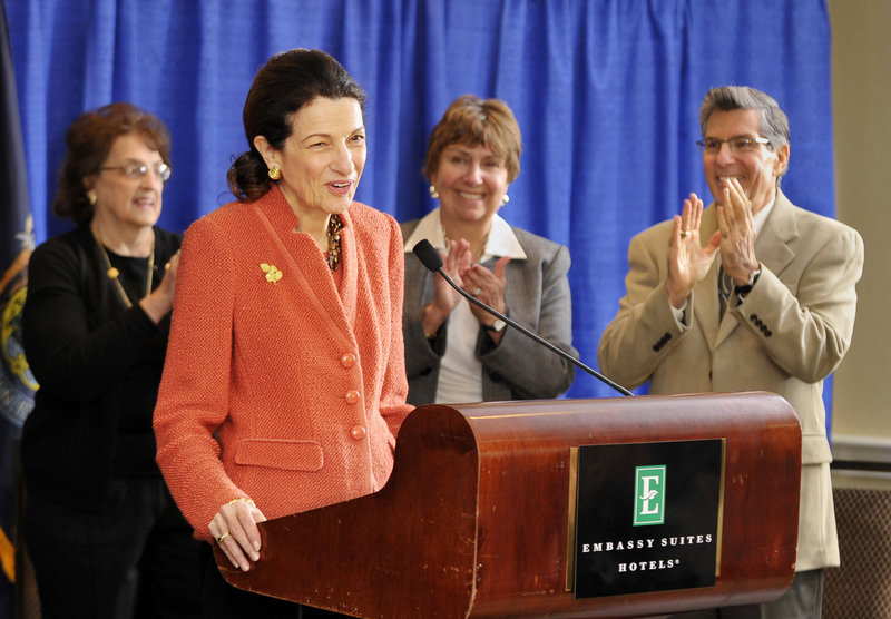 Sen. Olympia Snowe gets a standing ovation from family and friends Friday as she begins a news conference at the Embassy Suites hotel near the Portland International Jetport to talk about her decision not to run for another term.