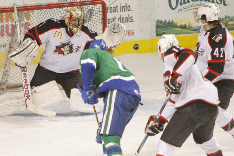 Pirates goalie Justin Pogge flashes out his glove to make a save on a shot by Kris Newbury of the Connecticut Whale. Pogge finished with 26 saves, and Portland got two third-period goals for a 3-2 victory.