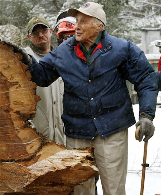 "In this Jan. 19, 2010 file photo, Frank Knight puts his hand on New Englandís tallest elm tree, known as ""Herbie,"" after it succumbed to Dutch elm disease and was cut down in Yarmouth, Maine. Knight, who took care of the tree for five decades while working as the Yarmouth tree warden, died in Scarborough, Maine, Monday, May 14, 2012. He was 103. (AP Photo/Pat Wellenbach, File)"