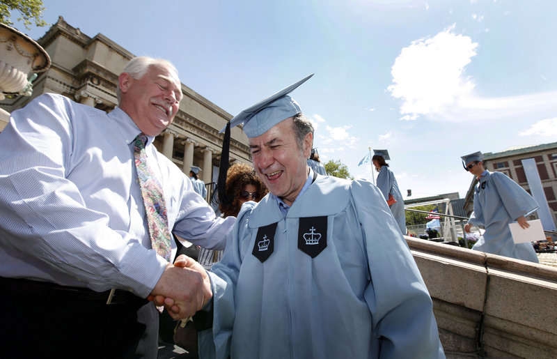 Columbia University janitor Gac Filipaj, center, is congratulated by his boss, Donald Schlosser, the assistant vice president of facility operations, during the Columbia University School of General Studies graduation Sunday in New York. Filipaj, an ethnic Albanian who left his native Montenegro 20 years ago to escape war, graduated with honors after 12 years of balancing studies and his full-time job.
