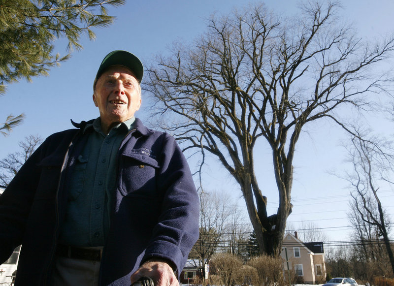 """Frank Knight stands in front of what was then New England's oldest elm tree, """"Herbie,"""" in 2009. Knight took care of Herbie for five decades, and when the diseased tree had to be cut down in 2010, he said, """"Nothing lasts forever. We had a great, beautiful relationship."""""""