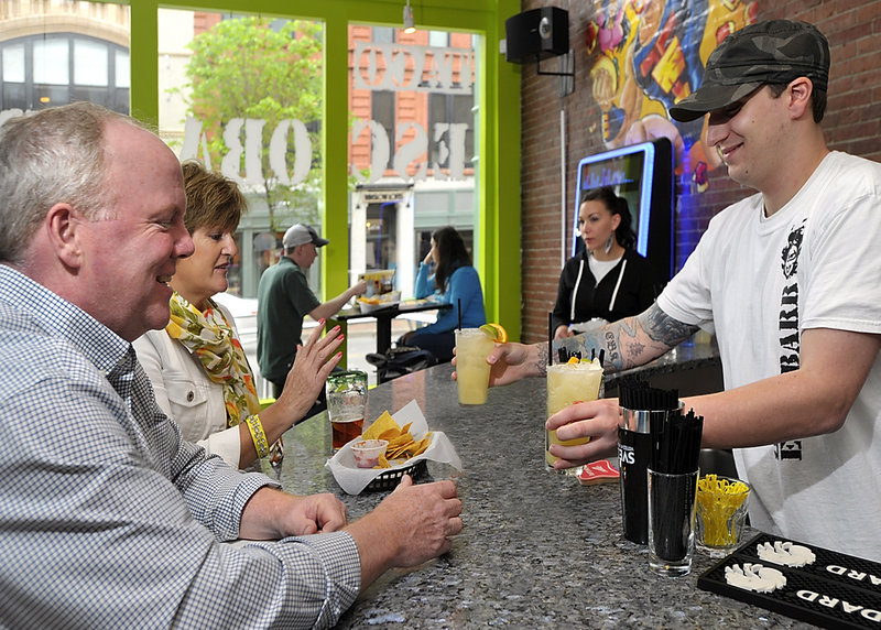 Bartender Eric Kreidler delivers margaritas to Doug and DeeDee Norton of Scarborough at Taco Escobarr, 548 Congress St., Portland.