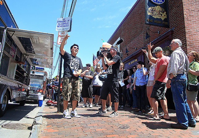 Ted Kim, center, leads the gathering crowd in a cheer just before opening the Seoul Sausage truck as The Great Food Truck Race is filmed for The Food Network in Portland outside of Ri Ra's Irish Pub on Commercial Street Sunday, June 17, 2012.