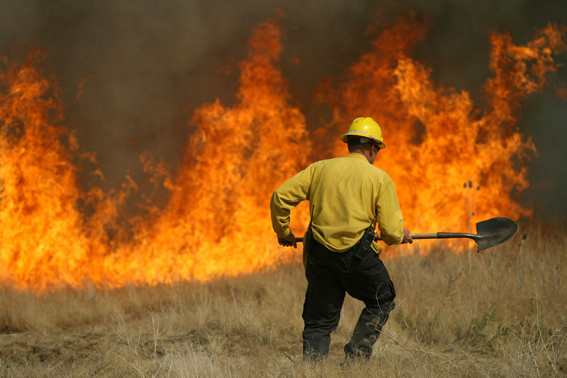 A member of the Rock Creek Rural Fire Protection District battles a blaze near the Hidden Lakes subdivision last week in Twin Falls, Idaho. Over the last 10 years, the wildfire season, which normally runs from June to September, has expanded to include May and October.