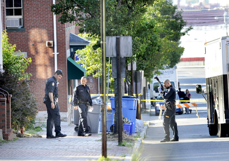 """Police collect and photograph evidence outside 105-107 India St. Angelina Badalucco, who lives at the address, said people often hang out in a concrete area in the back of the apartment building, drinking and smoking. """"I'm not surprised there was a confrontation and someone happened to have a weapon,"""" she said."""