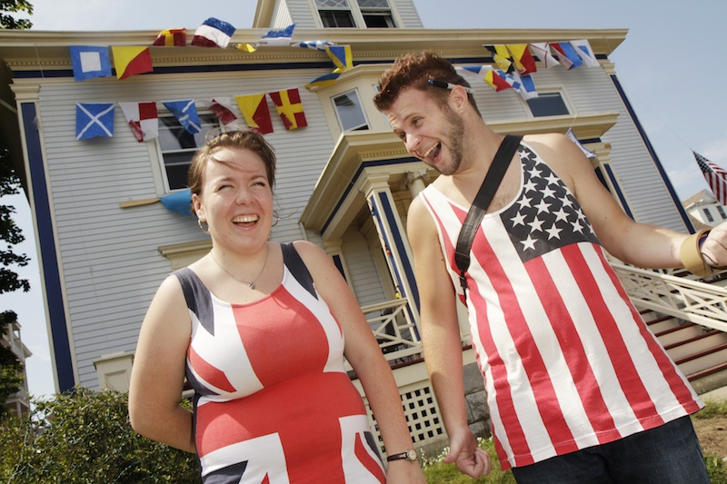 Madeleine Paine and Jake Hancock, dressed in flags, stand in front of Paine's home at 150 Eastern Promenade Ave. that was decorated for the Mumford & Sons concert on Saturday.