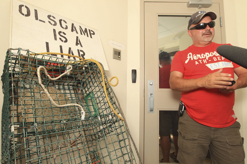 Protests in the Canadian Maritimes continued to escalate as more than 200 lobstermen converged on the offices of federal fisheries minister Keith Ashfield in Fredericton, New Brunswick, on Wednesday. Above, lobsterman Albert Hebert of Saint-Louis-de-Kent awaits access to the offices while, below, protesters attach signs to the entrance of the building. A meeting with Ashfield is scheduled Friday.