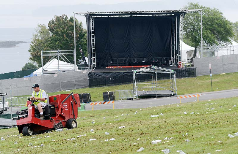 Robert Fogg of Portland Public Services Department cleans up trash with a turf sweeper on the hill at Eastern Prom Sunday. Fogg was one of many workers cleaning up following Saturday's Mumford & Sons concert.