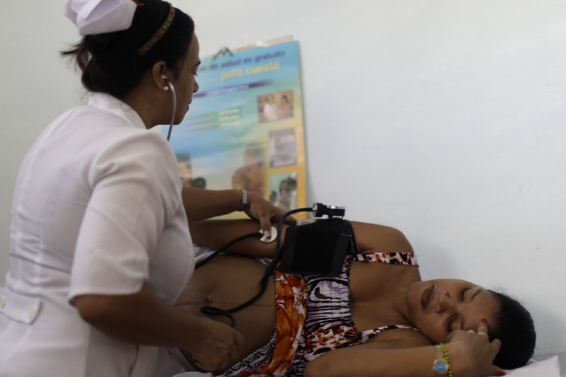 A nurse checks a pregnant woman's blood pressure at a government-run health clinic in Havana. An Associated Press article on health care in Cuba overlooks both the sector's accomplishments and the drawbacks of the U.S. system, a reader says.