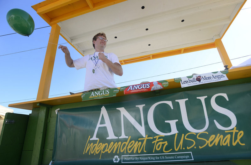 Ryan Boyd, field assistant with the Angus King for U.S. Senate Campaign, ties a balloon up to the campaign's fair booth at the Cumberland County Fair on Tuesday, Sept. 25, 2012.