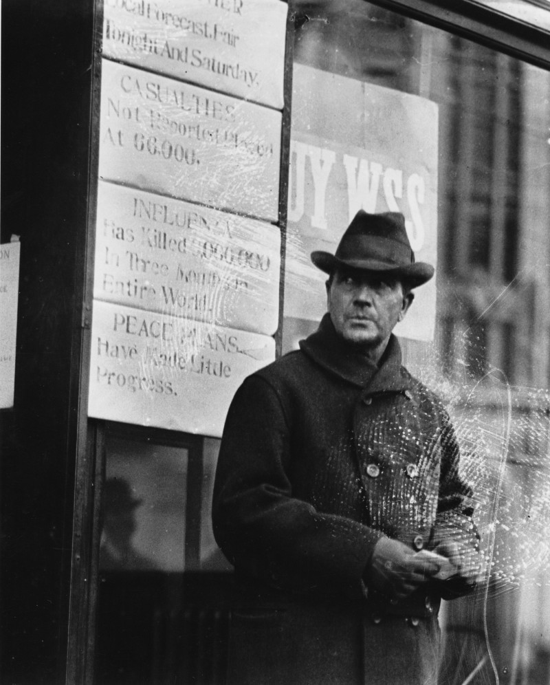 """A man stands outside of the Press Herald/Telegram building during World War I. One of the signs behind him reads, """"Influenza has killed 6,000,000 in three months in entire world."""" Credit: Gannett Collection, Maine Historical Society:"""