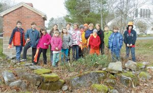 GEORGETOWN CENTRAL SCHOOL students stand around a historic foundation discovered in back of the school.