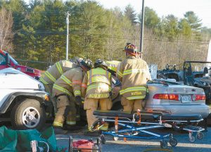 TOPSHAM FIREFIGHTERS work to free the driver of a car involved in a two-vehicle crash in the Topsham Fair Mall on Wednesday near Ruby Tuesday. Despite their efforts, the 79-year-old Brunswick woman died at the scene. The other driver was not injured.