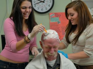 REGION TEN TECHNICAL HIGH SCHOOL firefighter instructor Dave Lewis earned cider and a doughnut for having his head shaved by health occupations students Gina Graziano and Miranda Lynch, who are working toward certification as certified nursing assistants at the Brunswick school.