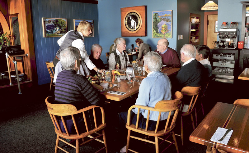 Waitress Sarah Dutil serves meals during lunch at The Last Unicorn restaurant in Waterville. This large group dined at the popular eatery during a birthday celebration for Tom Tietenberg, at head of table on right.