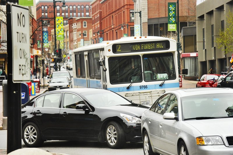 """A Portland Metro bus pulls out into traffic on Congress Street. Question 4, the transportation bond, """"includes $2 million to help replace Maine's aging fleet of transit vans and buses,"""" says a member of a transit group."""