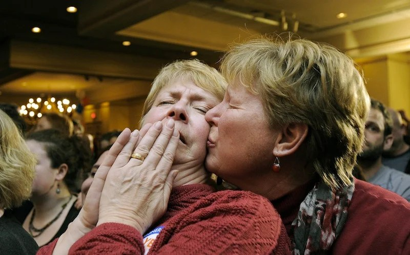 Ellie MacCallum, left, of Windham, receives a kiss from her partner, Judy Eycleshymer, right, after they learned same sex marriage had passed while at the Mainers United for Marriage party at the Holiday Inn by the Bay Tuesday, November 6, 2012. Marriage licenses for same-sex couples in Maine could be issued beginning Dec. 29.
