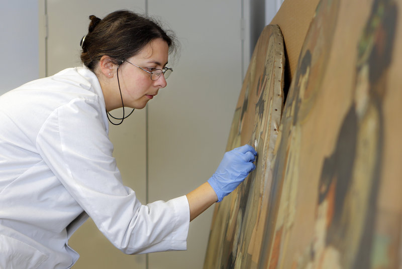 Katrina Jacques cleans a painting in Project MEAC's quarters in the State Theatre Building on High Street in Portland.