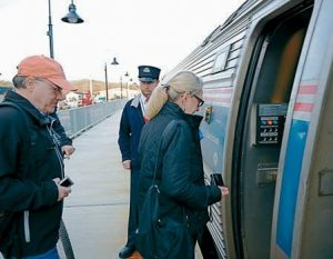 THE CROWD cheers as the Amtrak Downeaster filled with dignitaries arrives in Brunswick on Nov. 1. The next day, Brunswick-area residents Steven and Joanna Bradley, at right, and dozens of others board the train for its first day of regular service.