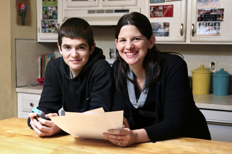 Janell Burley Hofmann is pictured with her son Gregory at their Sandwich, Mass., home. She holds a contract she drafted and Gregory signed as a condition for receiving his first Apple iPhone.