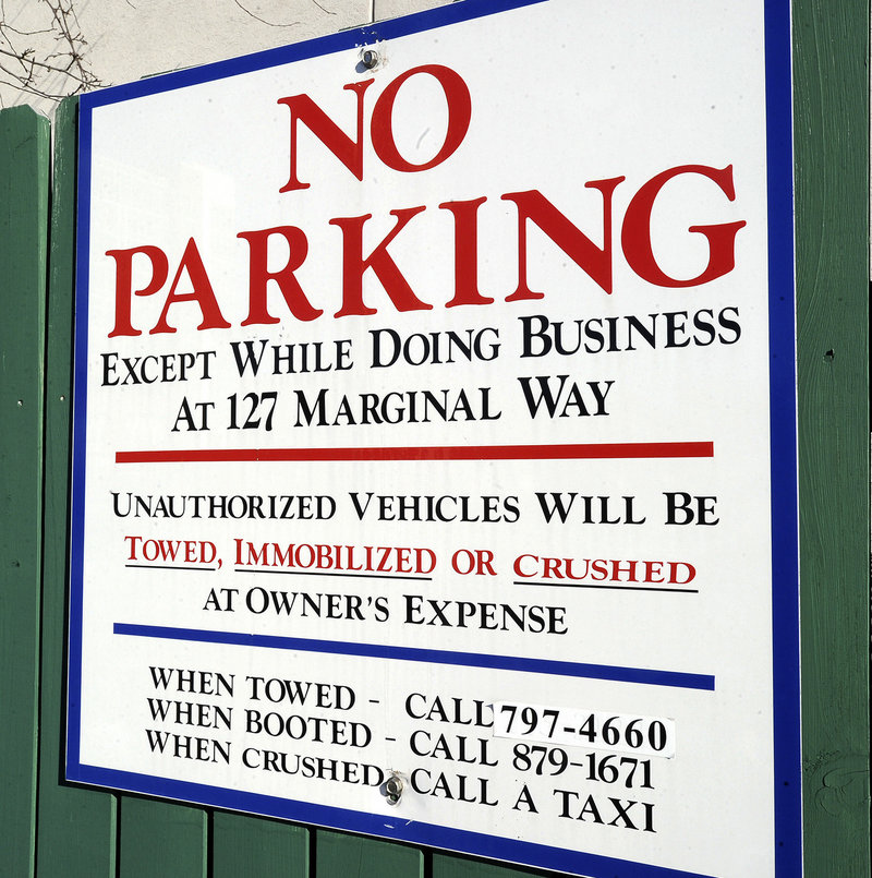 """A sign posted next to West Marine at 127 Marginal Way warns drivers not to park in the lot unless they're visiting the boating supply store or other businesses at the address. Trader Joe's shoppers who park there may find their car towed or booted – the """"crushed"""" threat was just a joke."""