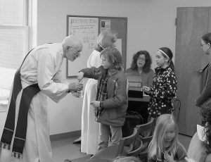 THE REV. CHUCK CARROLL offers communion during a Family Eucharist service at St. Paul's Episcopal Church in Brunswick. In the background is the Rev. Ann J. Broomell, former transition priest in charge.