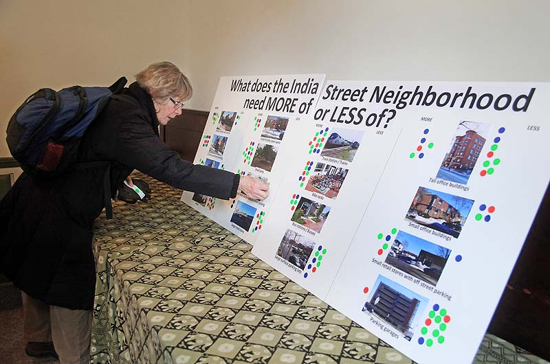 Elizabeth Streeter, a resident of Munjoy Hill in Portland, puts her opinion on a questionnaire board during an informal open house to consider the future of the India Street neighborhood, held at the Maine Jewish Museum on Saturday.