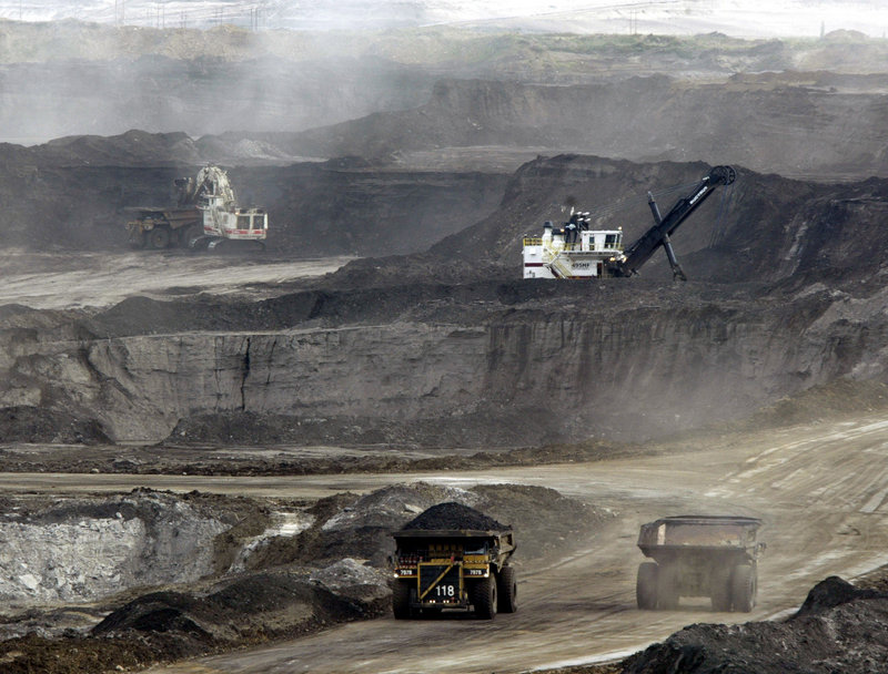 Mining trucks carry oil-laden sands at the Albian Sands project in Alberta, Canada, in 2005. Readers weigh the impact of piping tar sands oil through Maine.