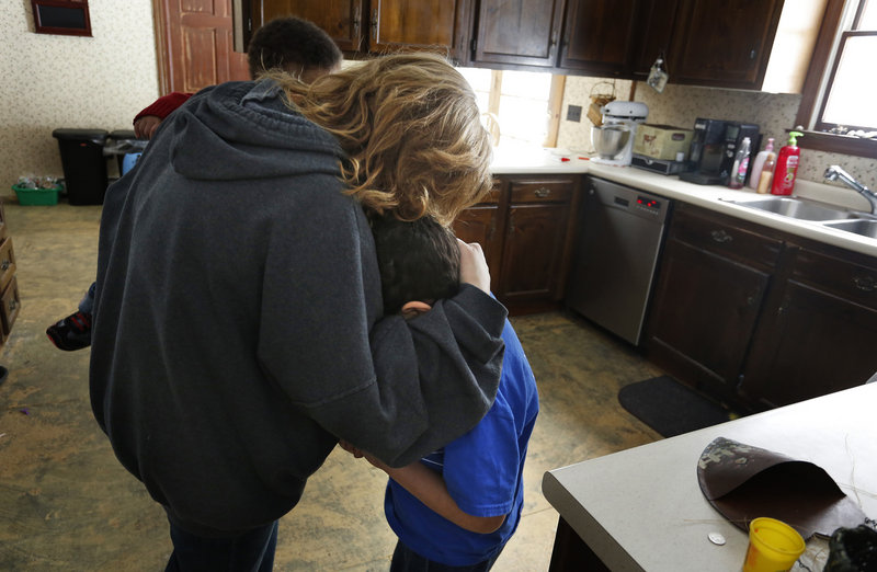 Marie Beaulieu comforts her son Shavar, 8, in their Jay home late last month, after he apologized for yelling at her. The Beaulieus adopted him after taking him in as a foster child.