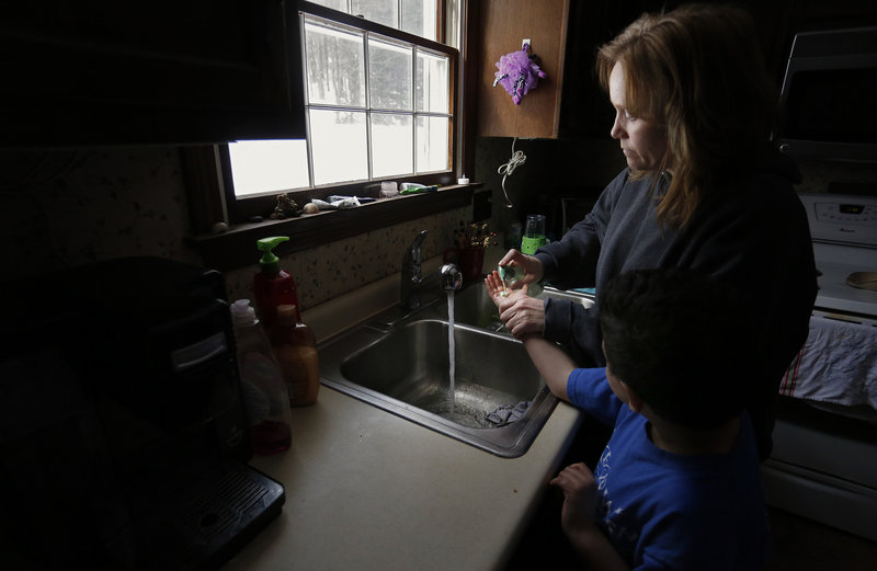 Marie Beaulieu of Jay helps her son Shavar, 8, wash his hands. She and her family adopted him after taking him in as a foster child. Lawmakers have backed spending cuts that affect support services for foster care adoptive parents like the Beaulieus, while regulators have failed to track long-term trends in foster care.