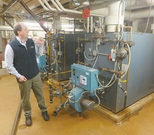 ERIK NORMAN, an engineering manager with Mechanical Services Inc., explains the workings of the natural gas boiler at Hyde School.