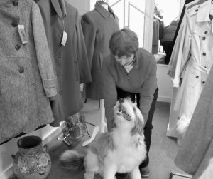 AMID CLOTHING OFFERINGS, Winters Gone owner Judy Taylor gives her collie, Tonto, some attention. The Wiscasset store has returned to its original location after spending nearly three years on Front Street in Bath.
